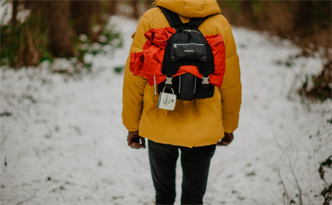 Walking on snowy track wearing yellow coat and small rucksack with coat and mug visible - Depression, Bolton CBT, Emma Yarwood